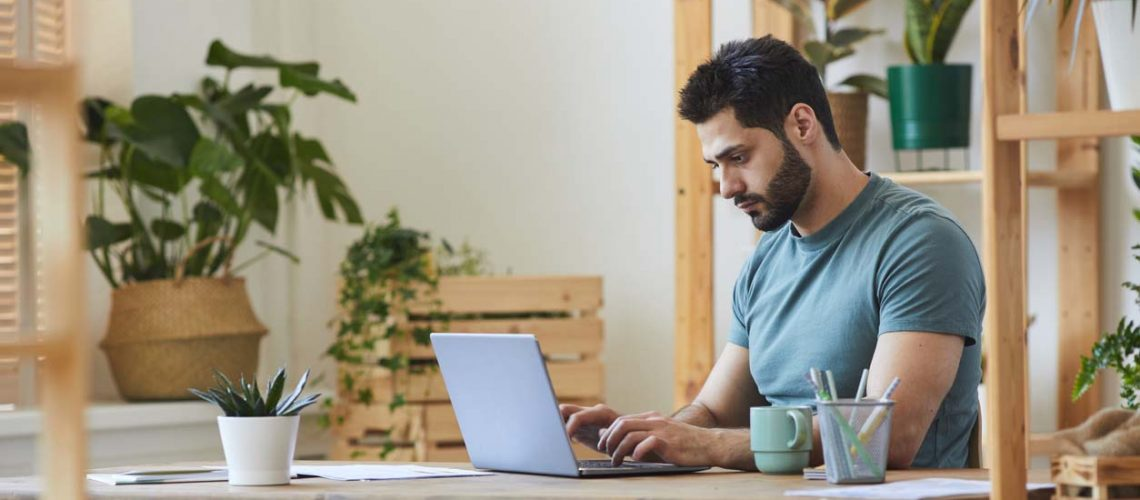 Side view portrait of handsome bearded man using laptop while sitting at desk in home interior decorated with houseplants, copy space